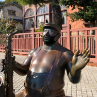 マスクをしたサックスを吹いている半裸の銅像